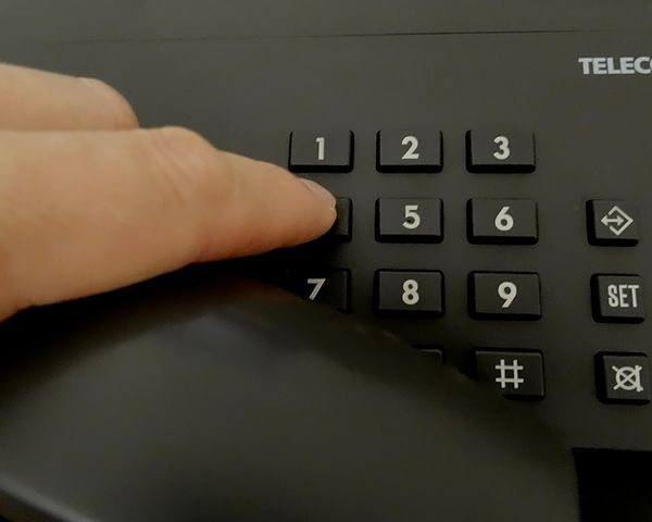 Person typing number into a telephone