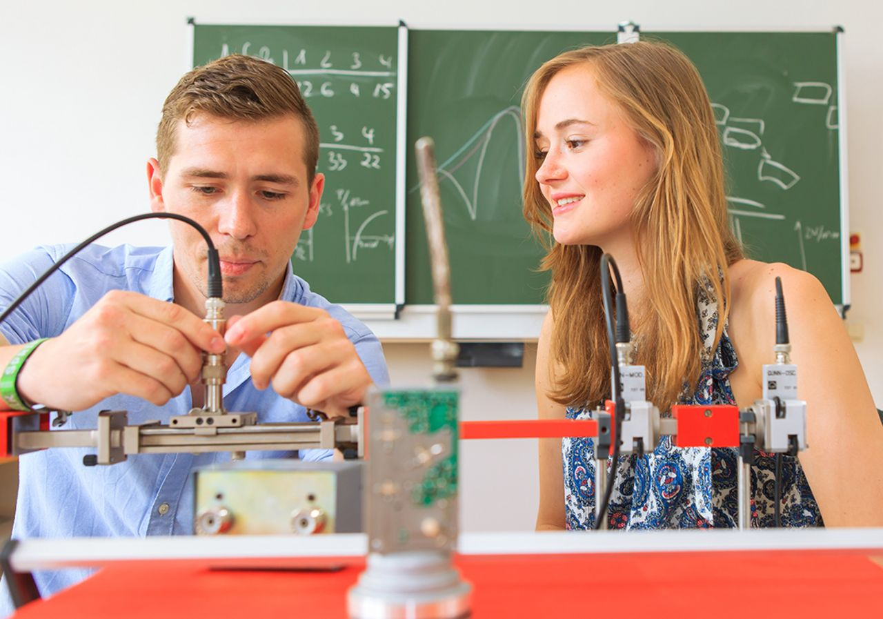 Two students do an electrotechnical experiment