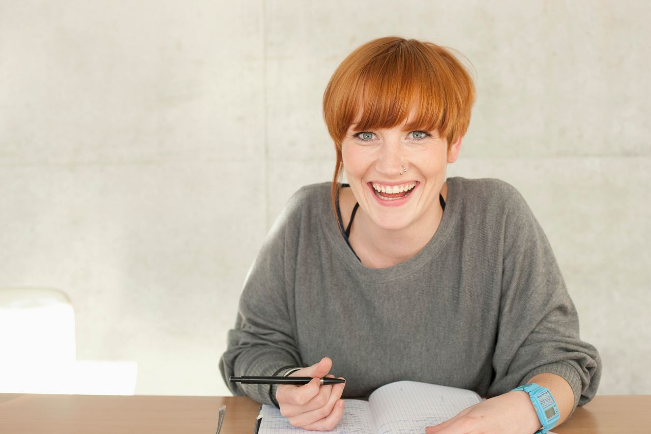 A student is sitting in front of a notebook with a pen in her hand and is smiling at the camera