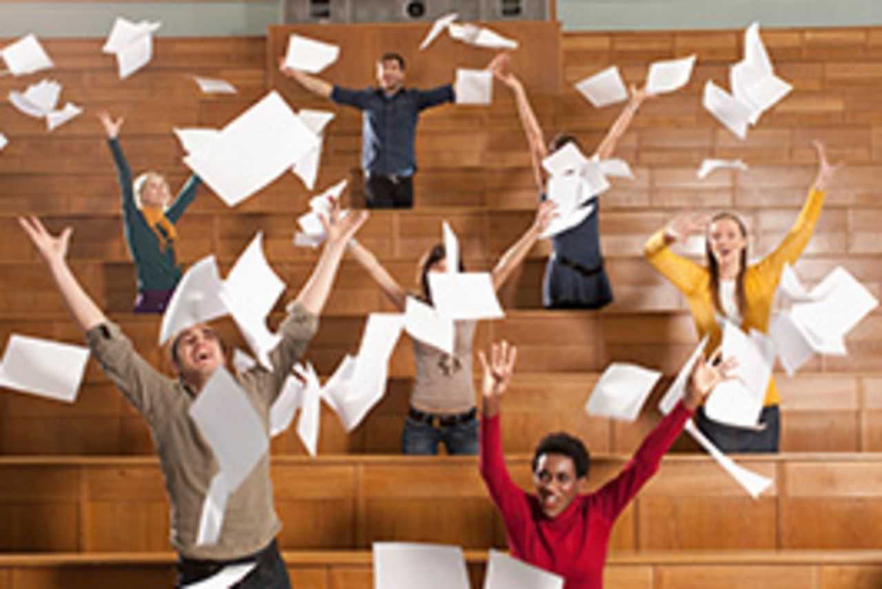 Students celebrate in a lecture hall and let their papers fly