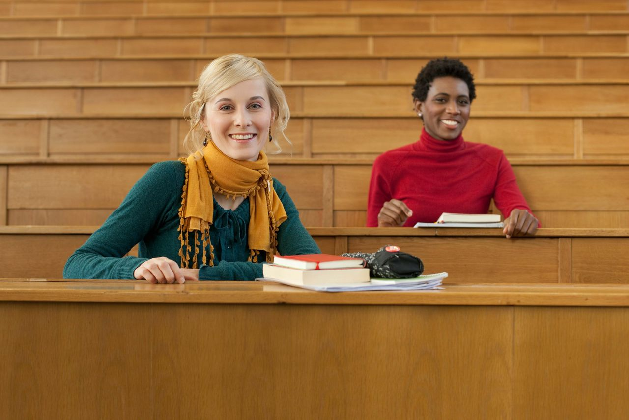 Two students sitting in a lecture hall and are smiling at the camera