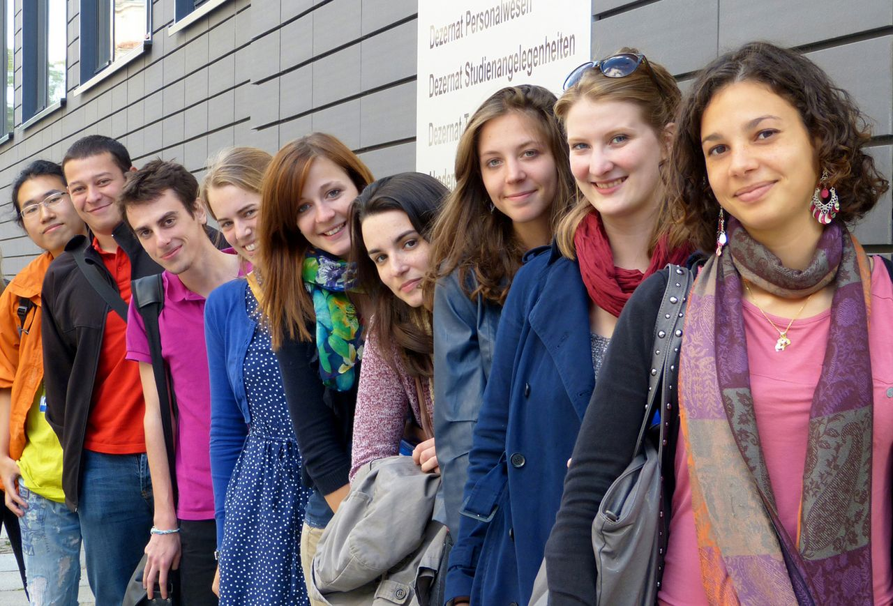 A group of international students stand in front of a HTWK Leipzig building