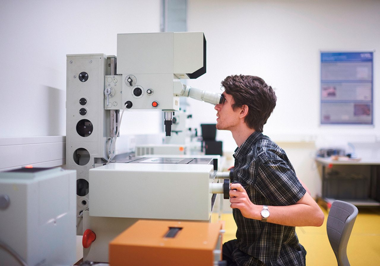 A student is looking into a big microscope