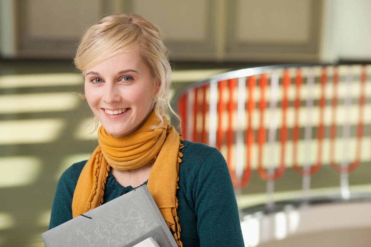 A female student smiles into the camera, holding some papers