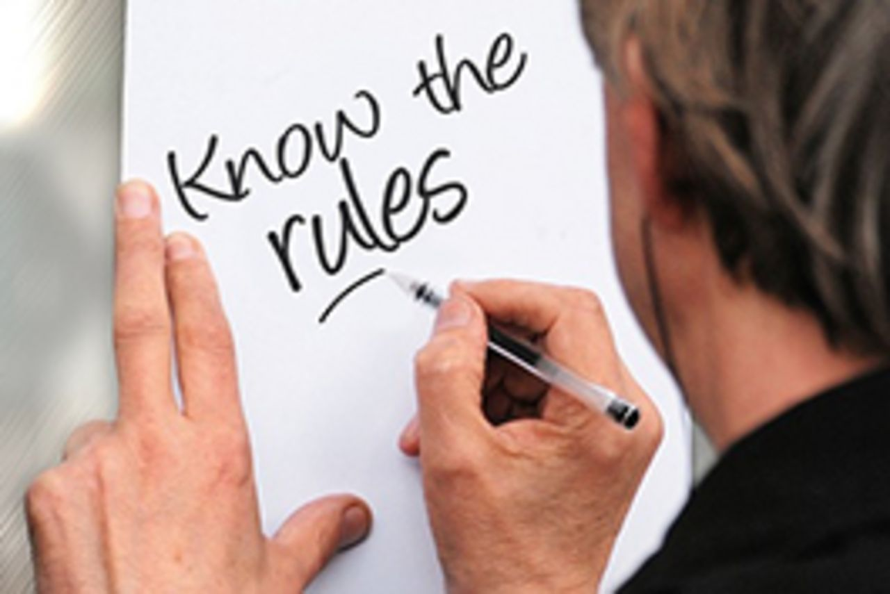 "A man is writing ""Know the rules"" on a paper"