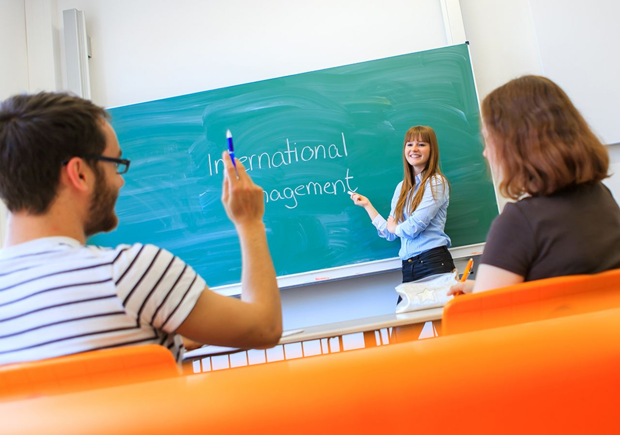 Three students are sitting in a classroom