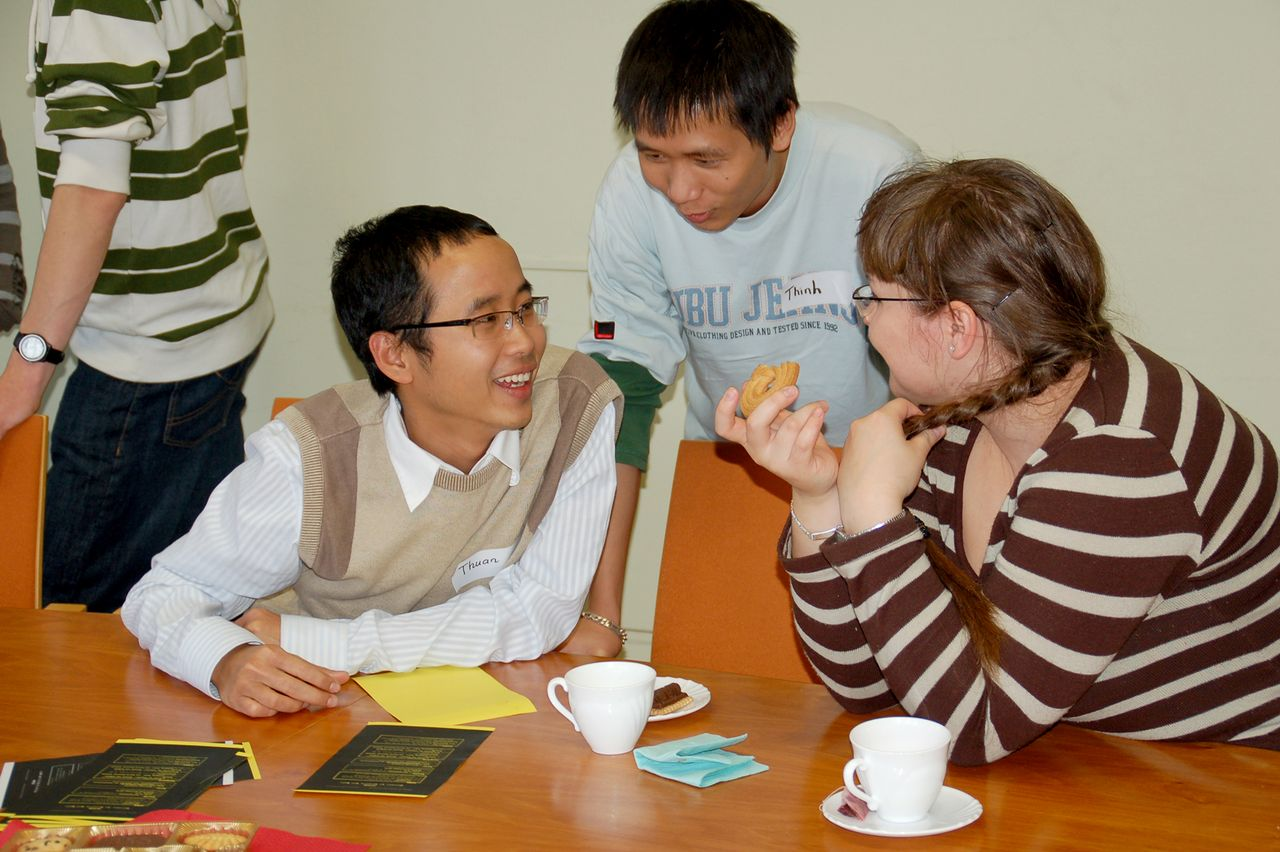 Three students have a chat while eating cake and drinking coffee