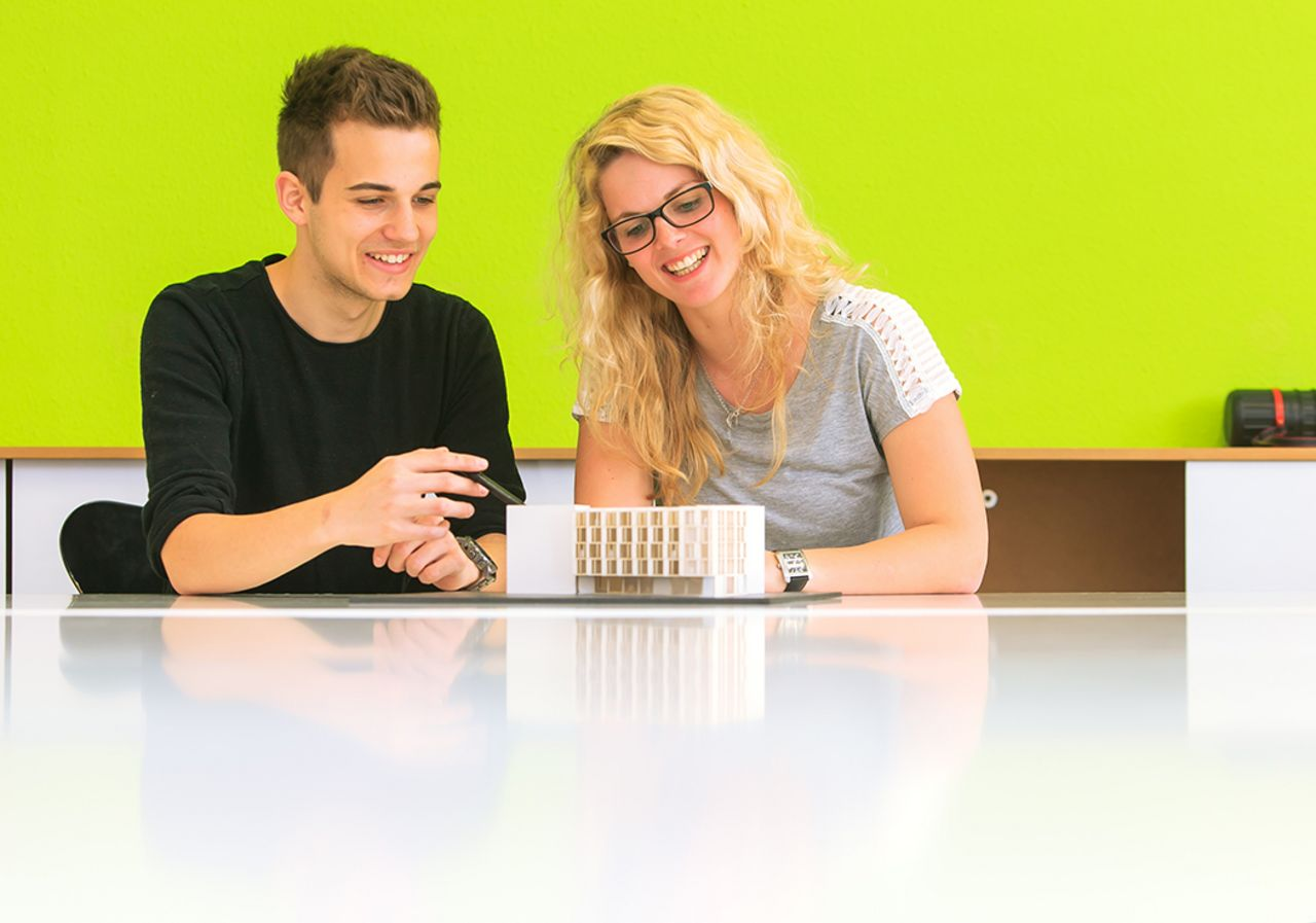 Two students discussing a model
