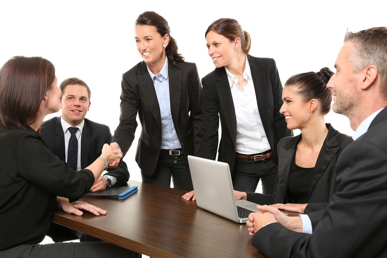 Six people in business suits meet at a table, four women and two men. Two of the women shake hands.